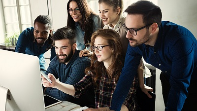 A group of people in front of a computer