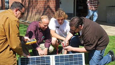 students and instructor around solar panel
