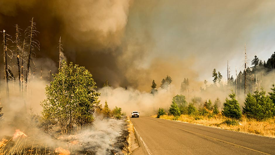 A truck driving down a rural road surrounded by wildfire smoke